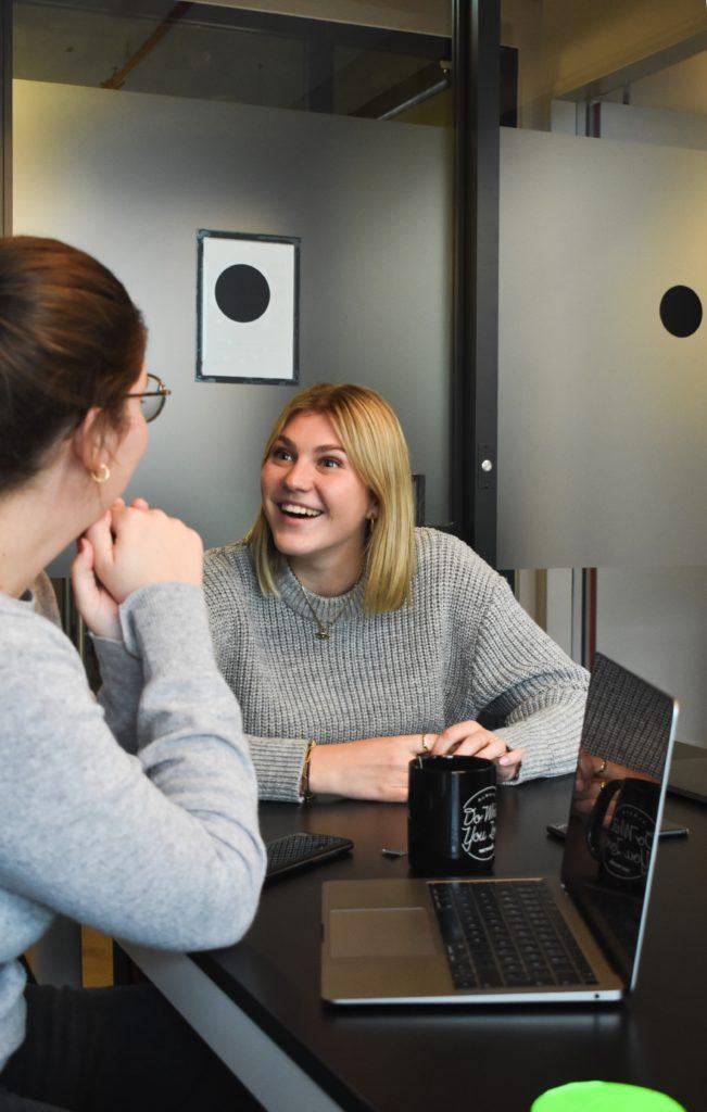 woman in gray sweater sitting beside woman in gray sweater
